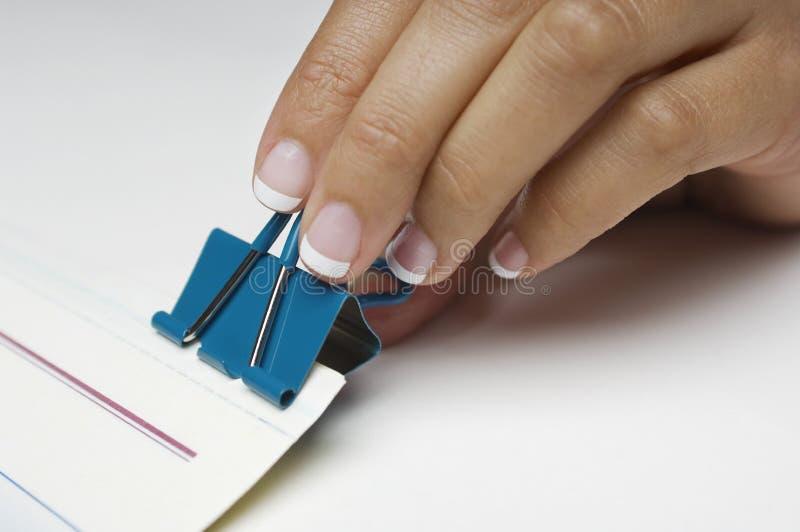 Hand som fäster det pappers- limbindninggemet arkivfoto