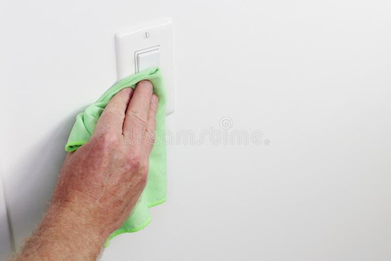 Hand som gör ren panelen för ljus strömbrytare med den gröna torkduken royaltyfri foto