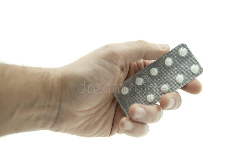 Hand som ger en minnestavla av vita piller på vit bakgrund royaltyfria bilder