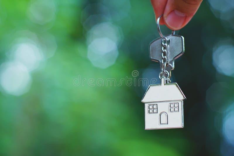 Hand som ger hem- tangent med förälskelsehuskeyringen med den gröna trädgården för suddighet, bakgrund, sött hem- begrepp arkivfoton