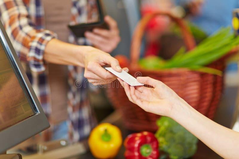 Hand som ger kreditkorten arkivbild