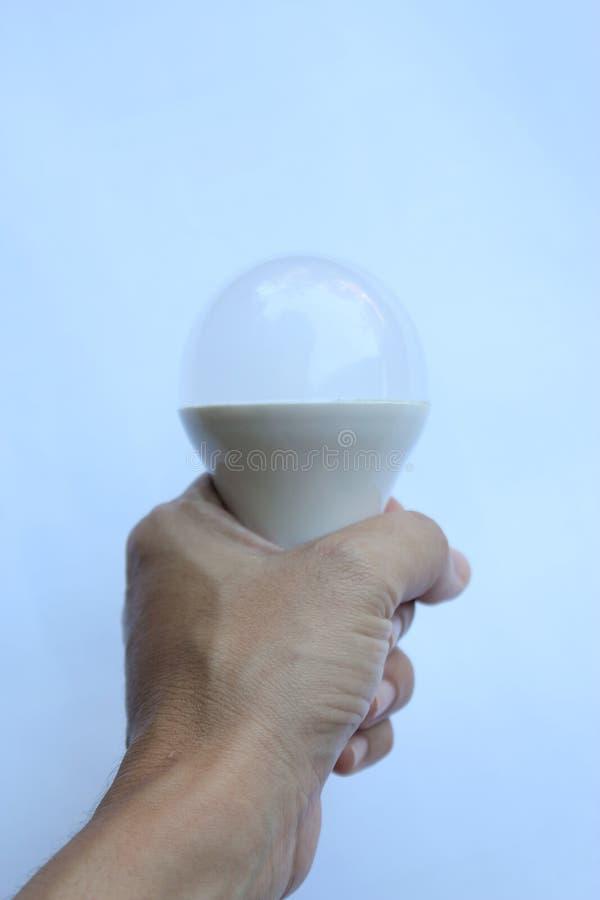 Hand som griper den vita ljusa kulan arkivbilder