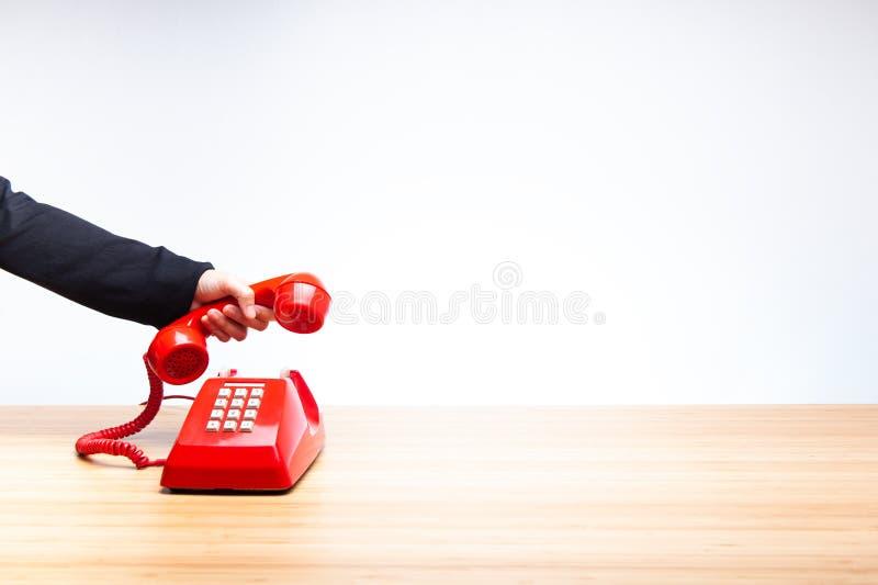 Hand som hänger upp den röda telefonen arkivfoto