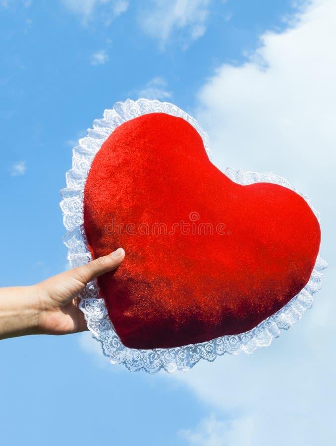 Hand som håller fast den hjärtformade kudden royaltyfria foton