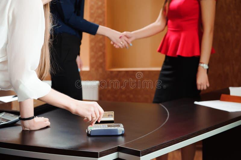 Hand som i regeringsställning som nallar debiteringkortet på pos.-terminalen, folk rymmer en konferens och diskuterar strategier royaltyfri bild