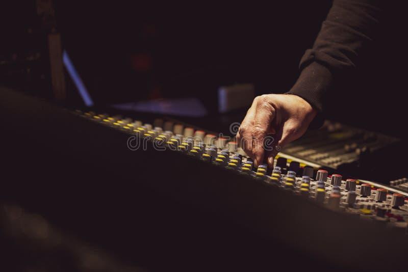 Hand som justerar ljudsignala glidare med den yrkesmässiga blandaren royaltyfri fotografi