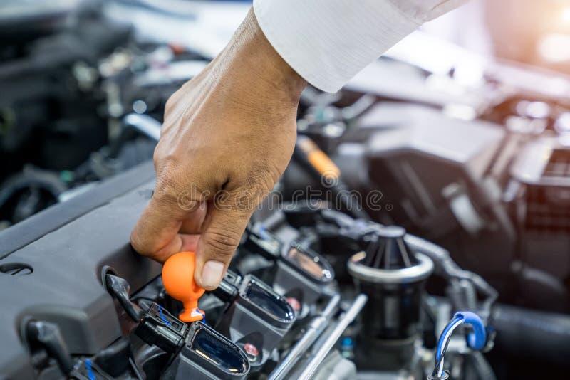 Hand som kontrollerar bilen för motorolja, arbete för automatisk mekaniker royaltyfria bilder