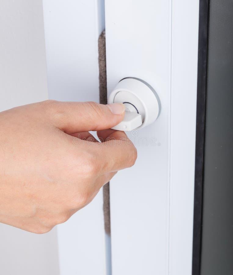 Hand som låser dörrknoppen av den glass dörren arkivfoto