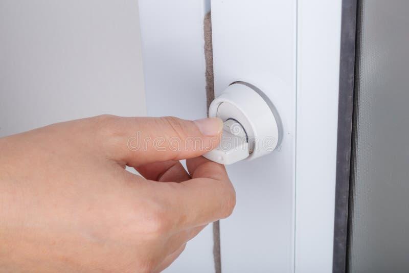 Hand som låser dörrknoppen av den glass dörren arkivbild