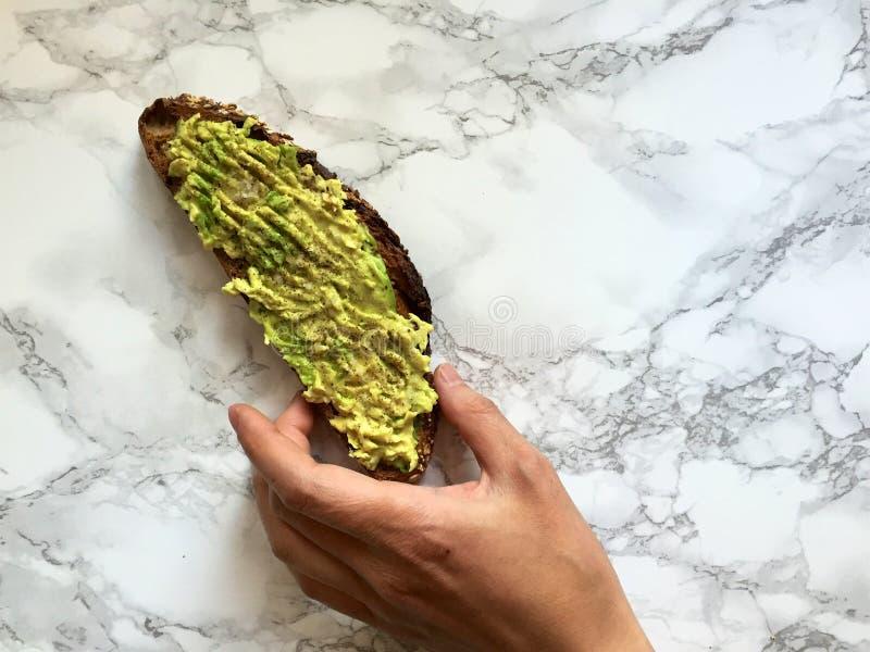 Hand som når för artisanal helt kornrostat bröd med avokadot, och salt hav arkivfoto