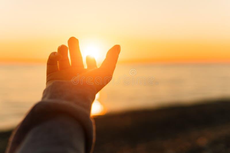 Hand som når för sol Solnedgångsol över havet arkivbild