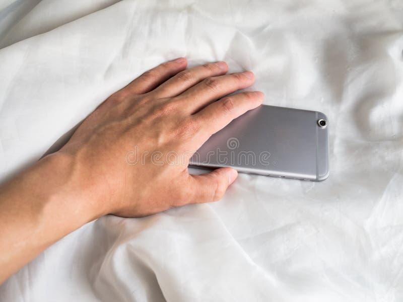 Hand som når för telefon i sängen royaltyfri fotografi