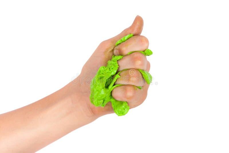Hand som pressar grön slam bakgrund isolerad white fotografering för bildbyråer