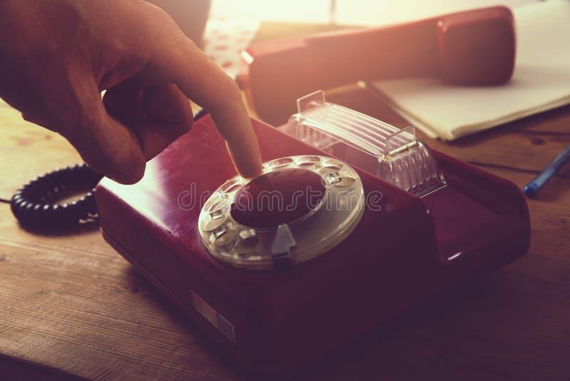 Hand som ringer den gamla retro roterande telefonen på trätabellen royaltyfri bild
