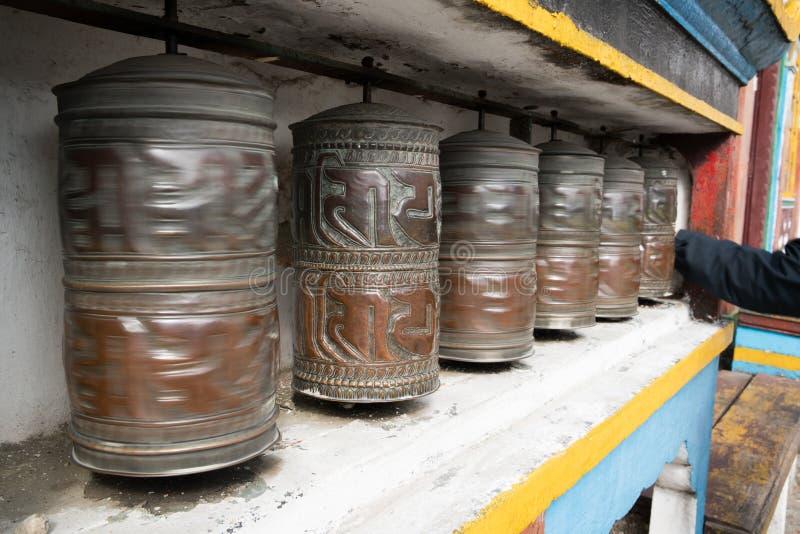 Hand som roterar rullande heliga tibetana bönhjul arkivbild