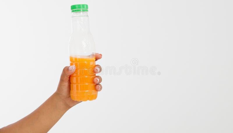 Hand som rymmer som är ny av den orange flaskan för fruktsaft som isoleras på vit bakgrund arkivbild