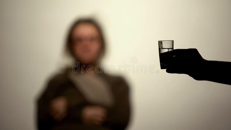 Hand som rymmer alkohol för drink för vodkaexponeringsglas erbjudande, böjelseviljekraft, rehab fotografering för bildbyråer