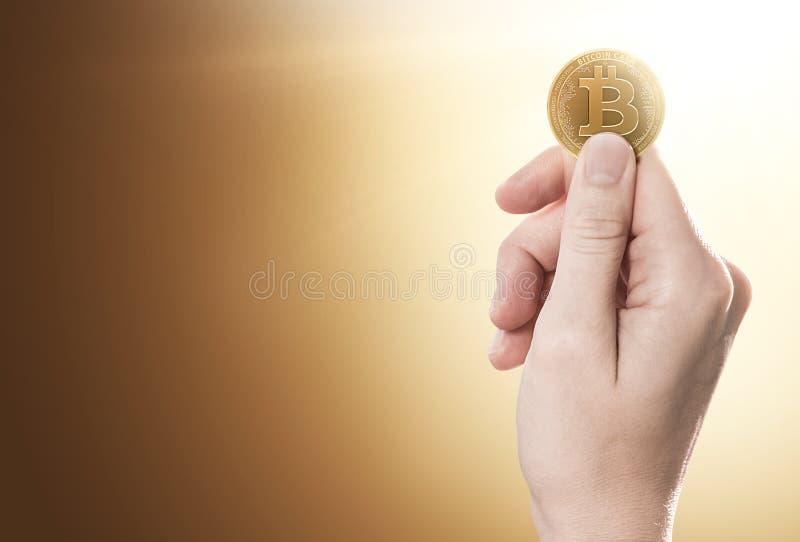 Hand som rymmer Bitcoin ett kontant mynt på en försiktigt tänd bakgrund med kopieringsutrymme arkivfoton