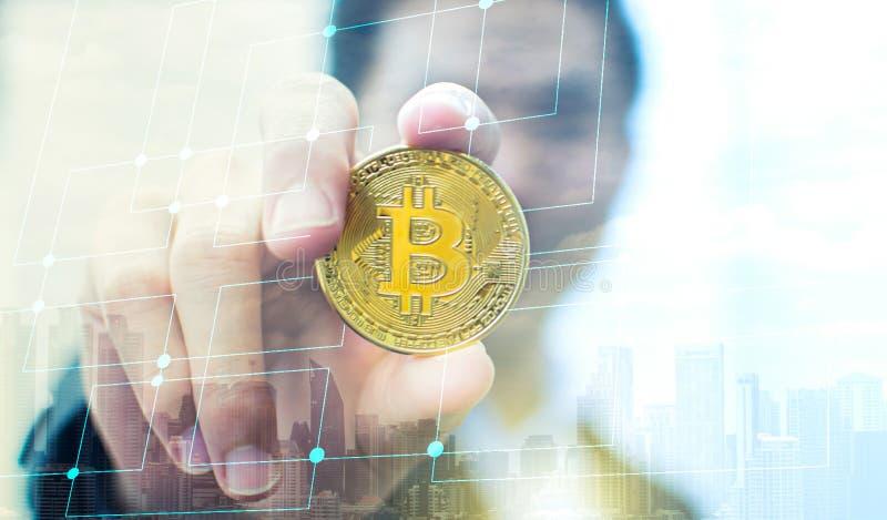 Hand som rymmer bitcoin med suddighetsbakgrund av affärsmannen royaltyfri fotografi