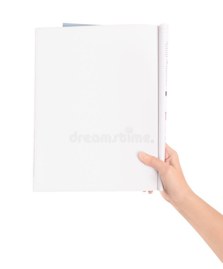 Hand som rymmer den blanka tidskriftsidan arkivbild