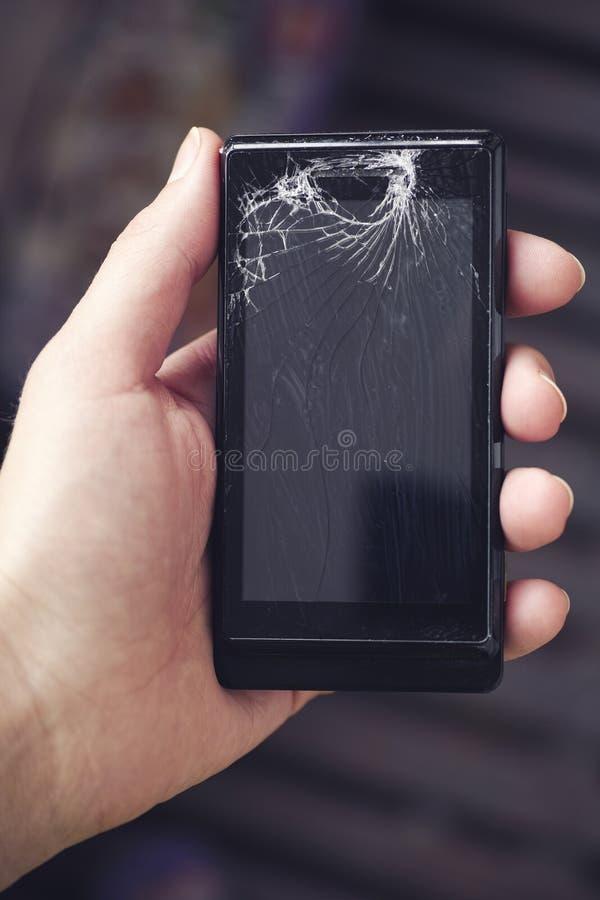 Hand som rymmer den brutna smartphonen arkivfoton