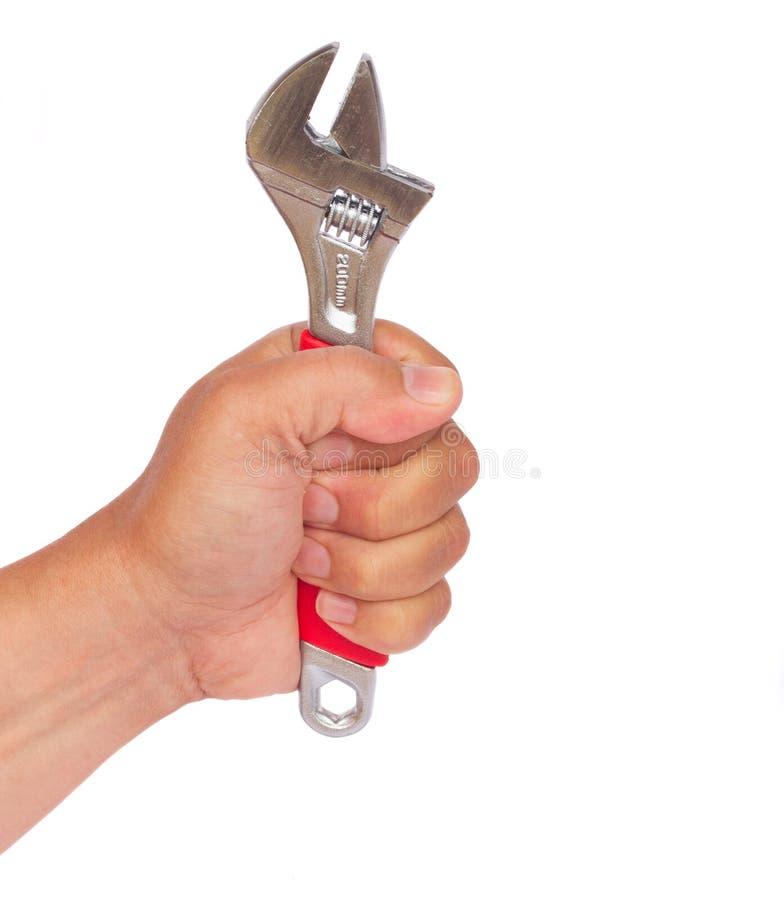 Hand som rymmer den justerbara skiftnyckeln arkivfoto