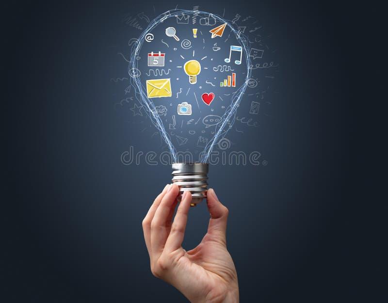 Hand som rymmer den ljusa kulan med apps royaltyfri illustrationer