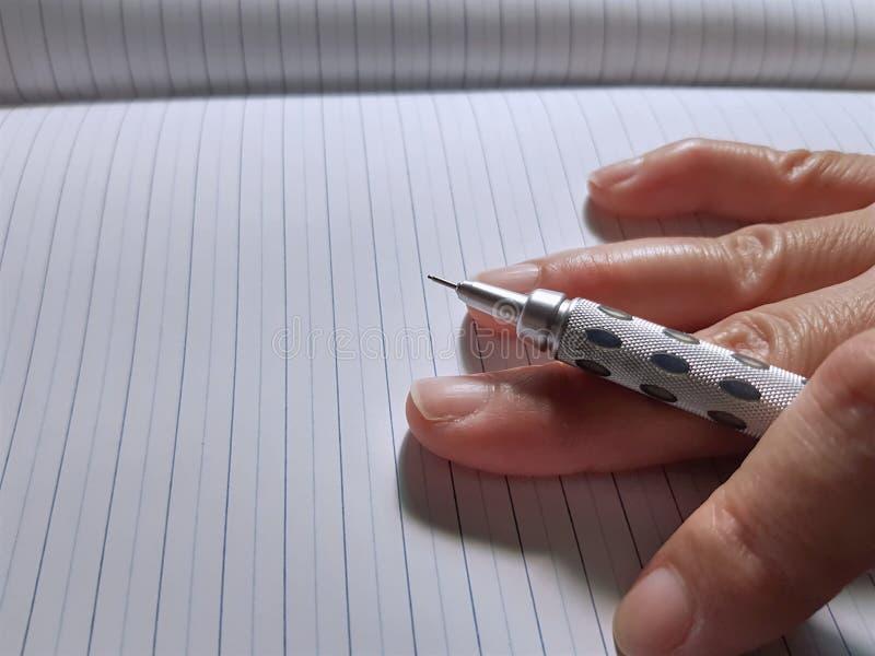 Hand som rymmer den mekaniska blyertspennan på anteckningsbokpapper royaltyfria foton