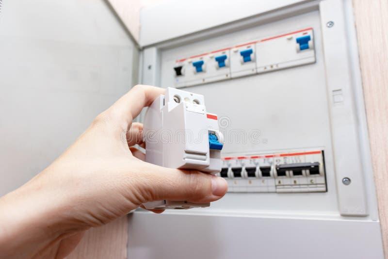 Hand som rymmer den nya automatiska strömbrytaren och den suddiga elektriska skölden med automatiska strömbrytare av elektricitet arkivbilder