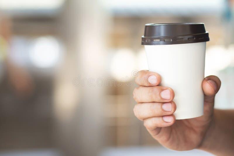 Hand som rymmer den pappers- koppen av tagandet som dricker bort kaffe p? naturligt morgonsolljus arkivbilder