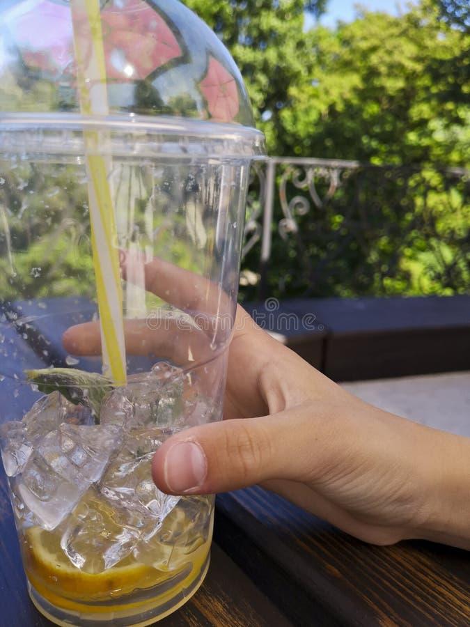 Hand som rymmer den plast- koppen för lemonad med sugrör royaltyfri bild