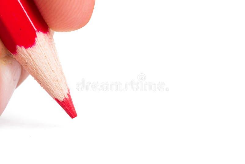 Hand som rymmer den röda blyertspennan royaltyfri fotografi