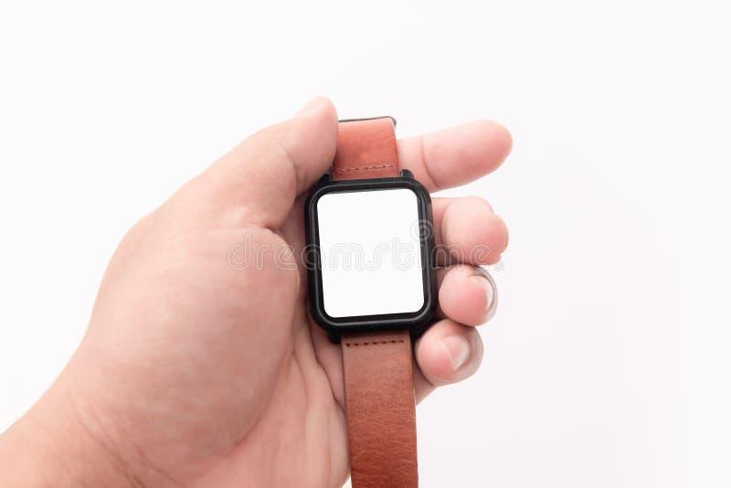 Hand som rymmer den smarta klockan med bruna remmar för äktt läder arkivbild