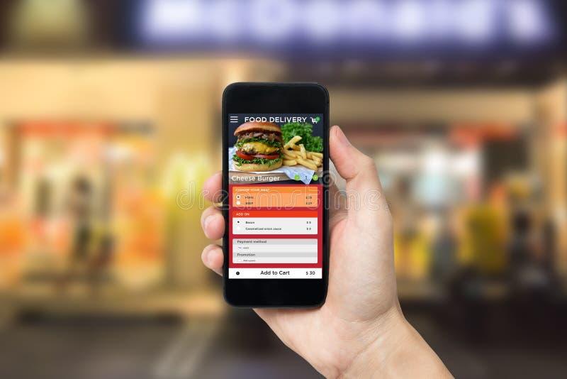 Hand som rymmer den smarta telefonen med skärmen för beställning för appmatleverans applikation för restaurangservice royaltyfria foton