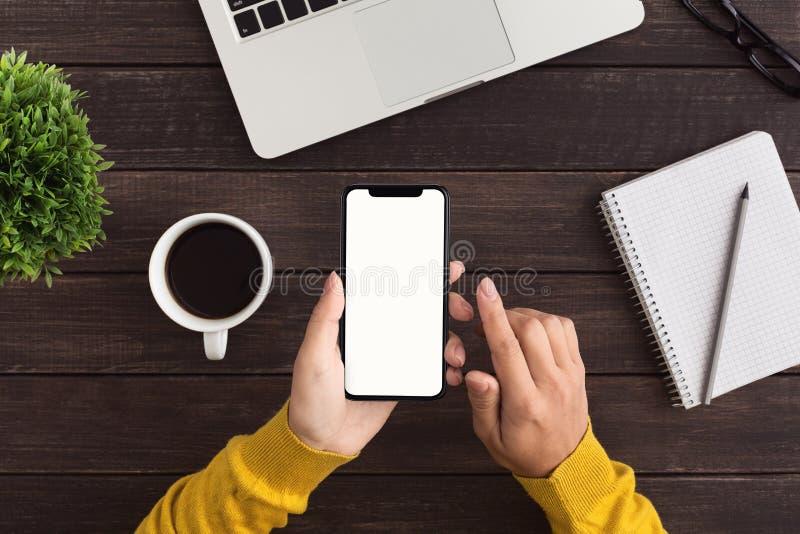 Hand som rymmer den smarta telefonen som söker för informationsloppplan arkivfoto