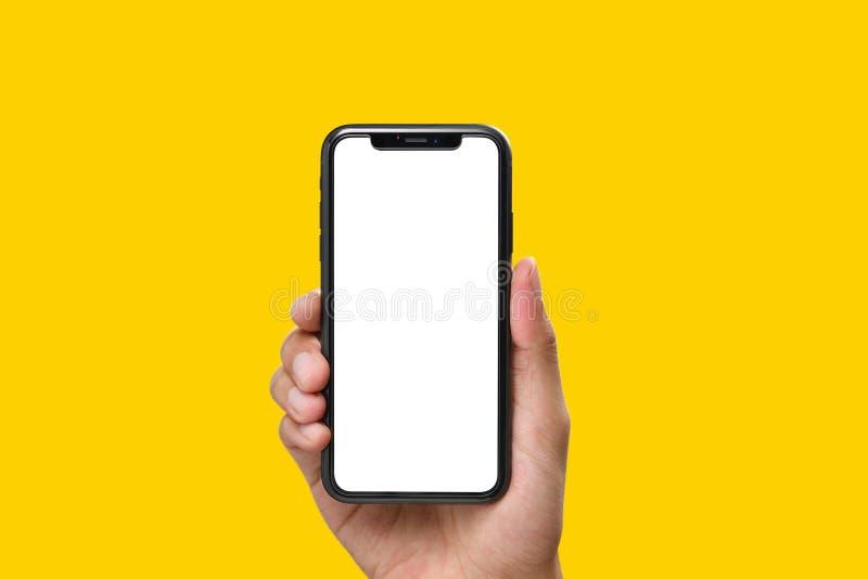 Hand som rymmer den svarta smartphonen med den tomma skärmen royaltyfri fotografi