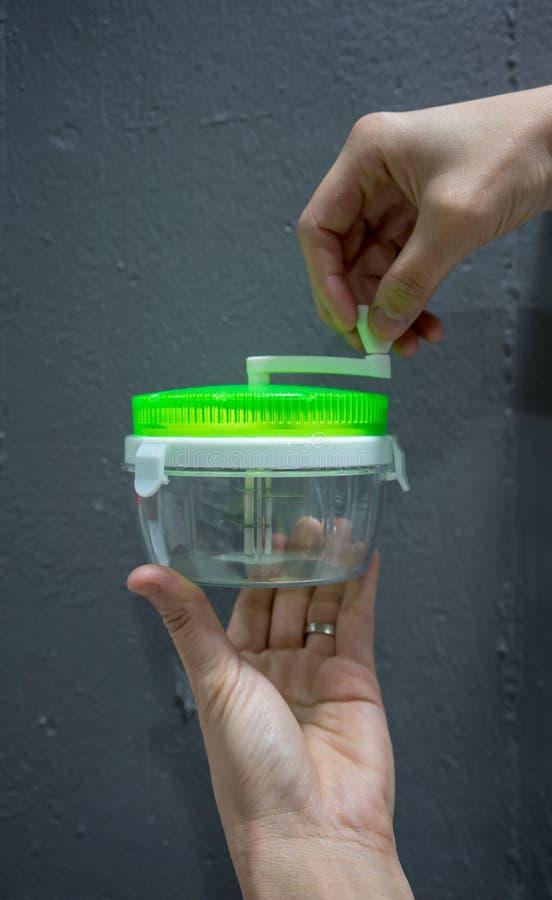 Hand som rymmer den tomma plast- behållaren av mini- kökhjälpmedel för M royaltyfri fotografi