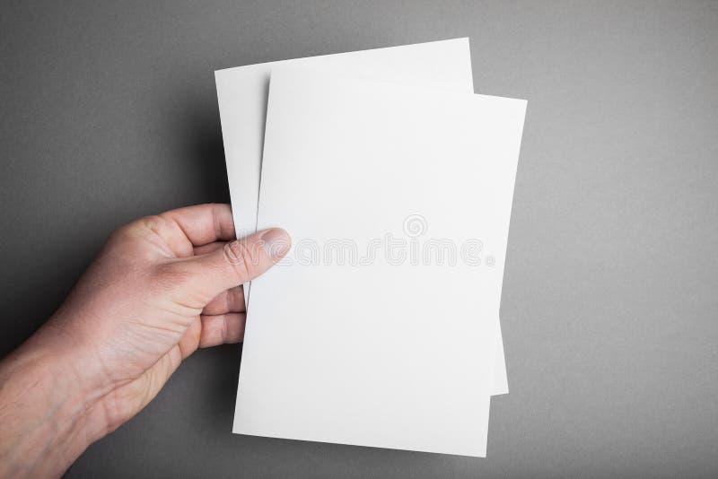 Hand som rymmer den vita arkmodellen för tomt papper A5 Design f?r broschyrdokumentyttersida royaltyfria foton
