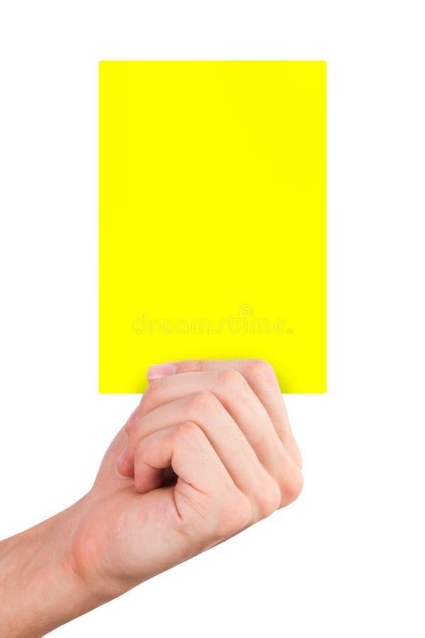 Hand som rymmer det gula kortet arkivfoto