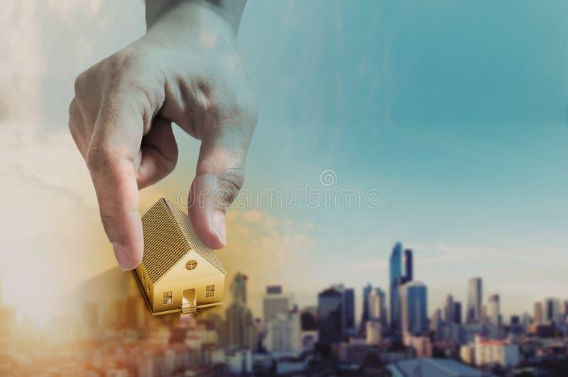 Hand som rymmer det guld- huset, fastighetsinvestering och köper husbegreppet, defocusstad i soluppgångbakgrund royaltyfria foton