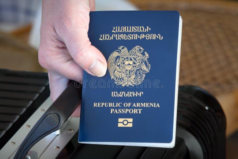 Hand som rymmer det Republiken Armenien passet royaltyfria foton