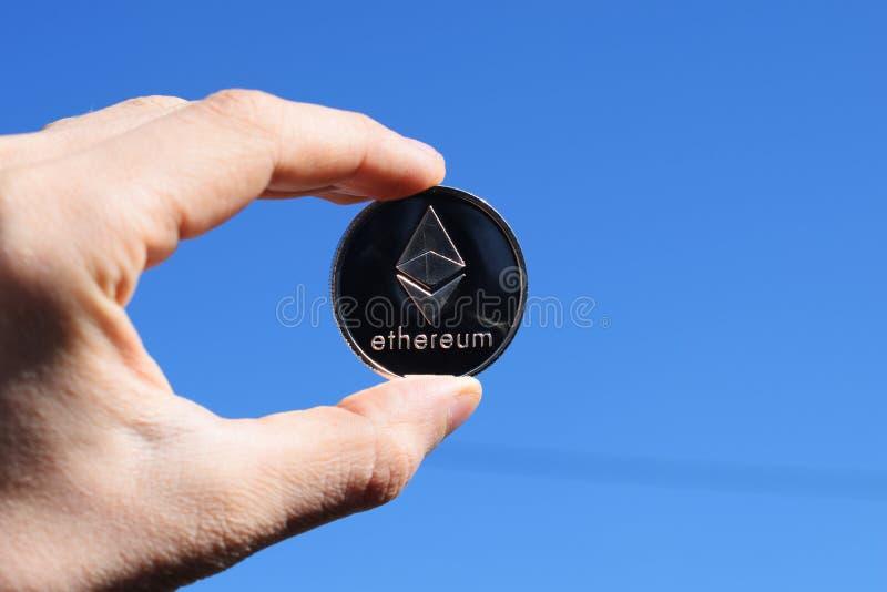 Hand som rymmer det silverEthereum myntet på bakgrund för blå himmel royaltyfria foton
