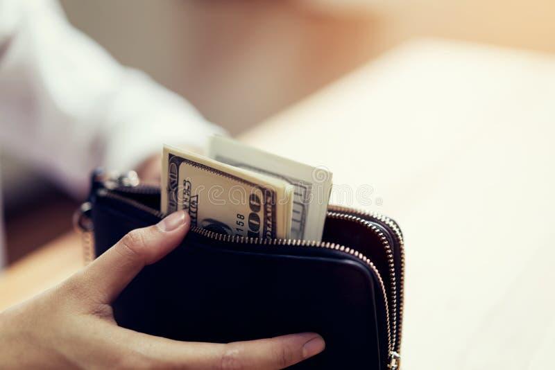Hand som rymmer 100 dollar räkningar i plånbok Begreppet av utgifter vid kassa arkivfoton