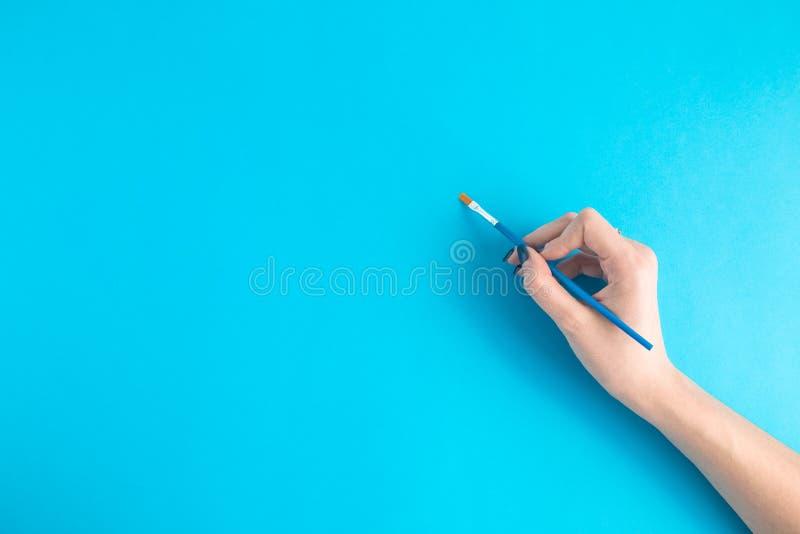 Hand som rymmer en borste på blå bakgrund royaltyfria foton