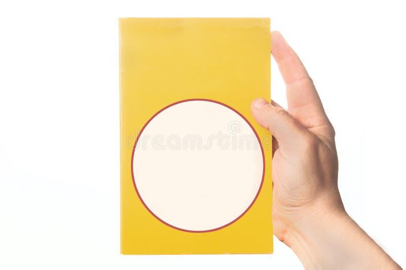 Hand som rymmer en brotts- ny bok med den tomma räkningen på vit bakgrund arkivbild
