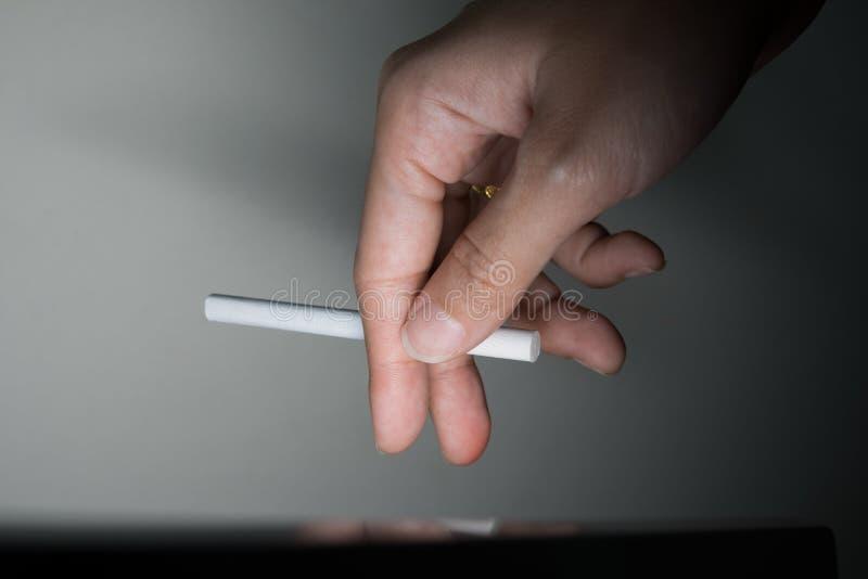 Hand som rymmer en cigarett arkivfoton