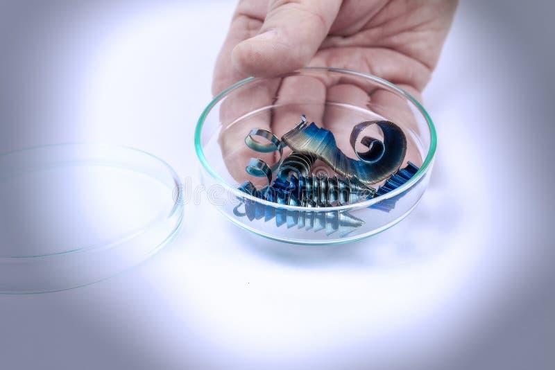 Hand som rymmer en exponeringsglasplatta med metallshavings arkivbild