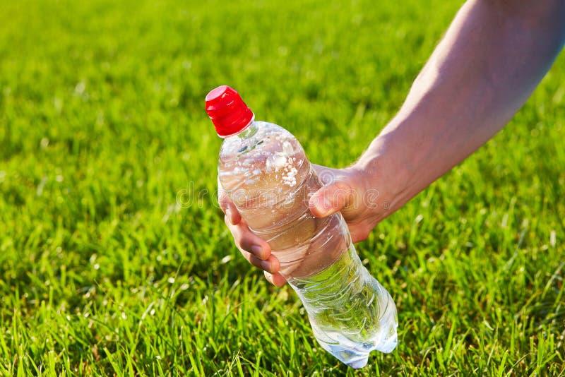 Hand som rymmer en flaska av rent vatten arkivfoton