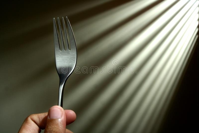 Hand som rymmer en gaffel royaltyfria foton
