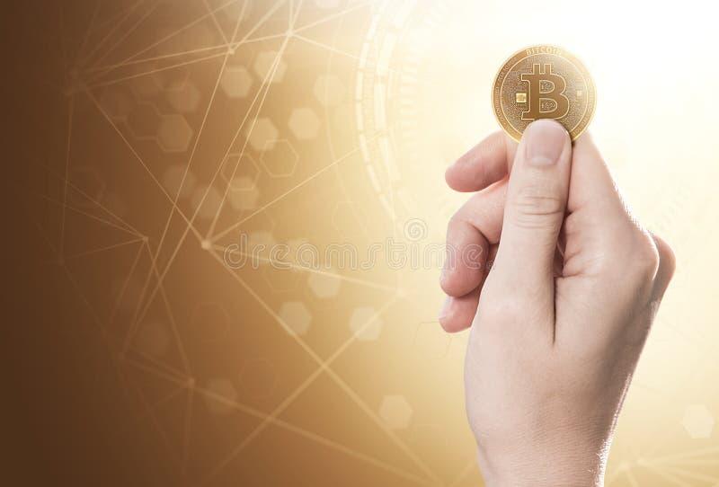 Hand som rymmer en guld- Bitcoin på en ljus bakgrund med blockchainnätverket arkivbilder